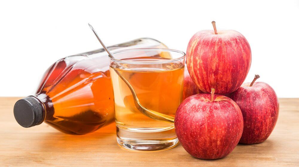 Apple cider vinegar in a jar with apples and a glass fileed with apple cidar vinegar