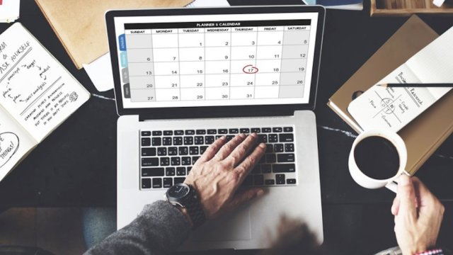 Man working on a Apple MacBook with calendar app open trying to be productive