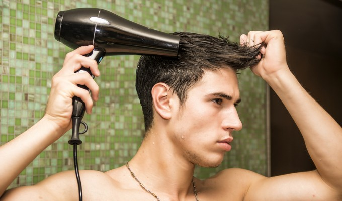 Boy drying wet hair with a blow dryer