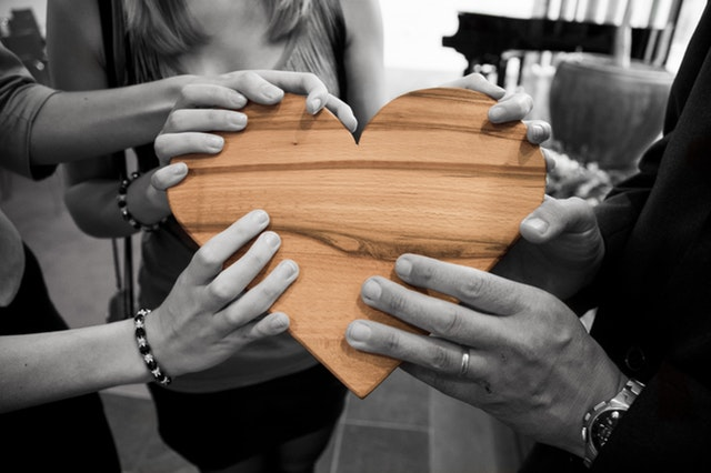 People holding heart made of wood in hands
