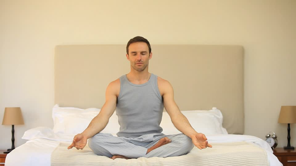 Man meditating at bed