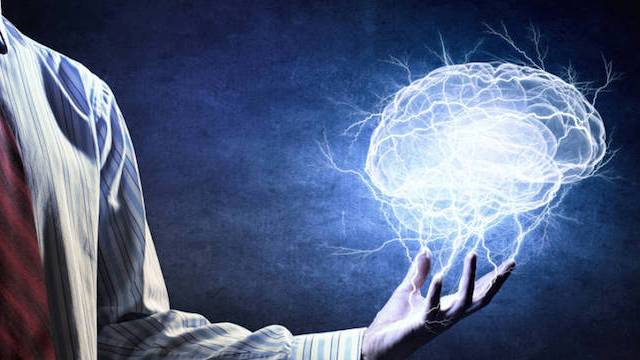 Photo of man manipulating mind for success with brain in his hand