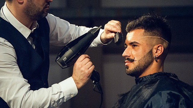 Man getting his hair blow-dried which can damage hair