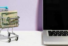 cart full of money alongside a laptop