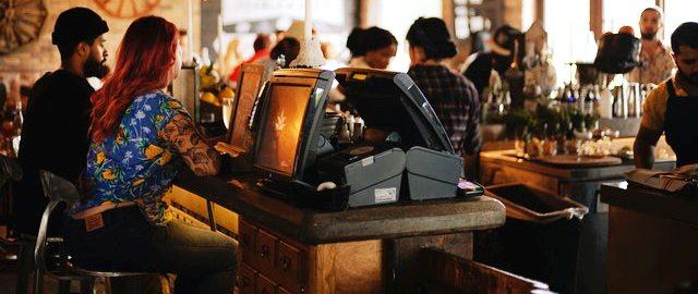 Cashier in front of Restaurant Management Software