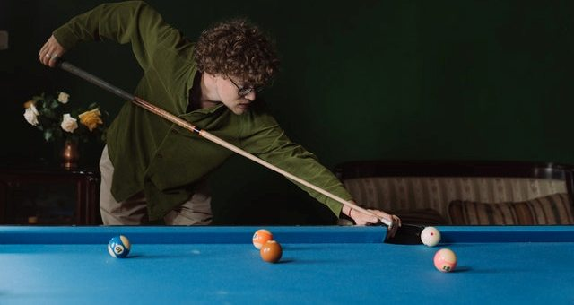 A guy playing snooker