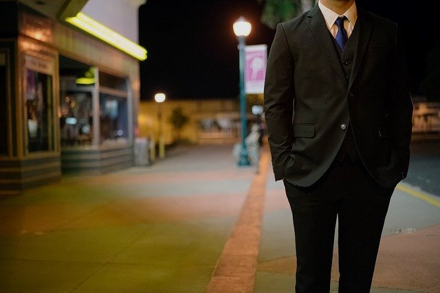 A man wearing a suit standing in a street