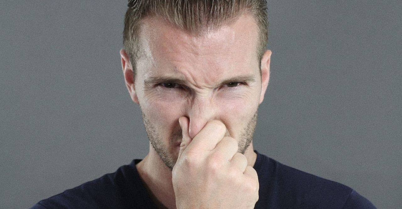 A man stopping his nose from smelling bad house smells