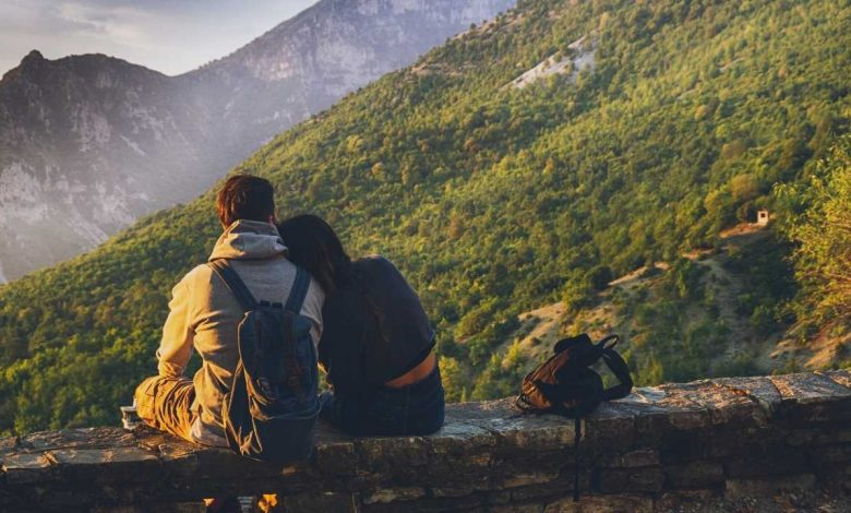 Couple sitting facing the mountains